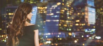 Femme regardant la ville de nuit Photo libre de droits
