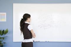 Femme regardant le griffonnage sur le tableau blanc image libre de droits