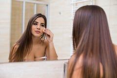 Femme regardant le miroir à la maison et appliquant la crème sur son visage Photos stock