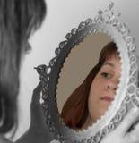 Femme regardant le miroir Photographie stock libre de droits