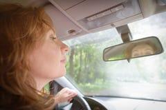 Femme regardant le miroir dans sa voiture image stock