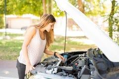 Femme regardant le moteur de sa voiture cassée image stock