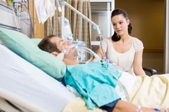 Femme regardant le patient critique se trouvant sur le lit photo stock