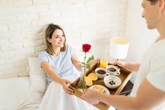 Femme regardant le petit déjeuner de portion d'ami à elle dans le lit photos stock