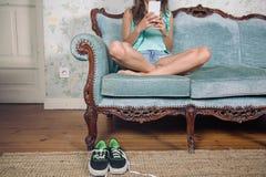 Femme regardant le smartphone se reposant sur le sofa avec des jambes Image stock