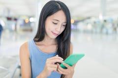 Femme regardant le téléphone portable dans l'aéroport Image stock