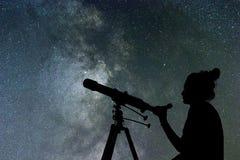Femme regardant les étoiles avec le télescope près de elle photo stock