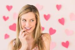 Femme regardant loin avec les papiers en forme de coeur contre Backgro rose photos stock