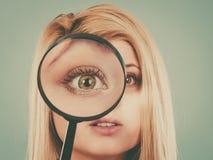 Femme regardant par la loupe Photos stock