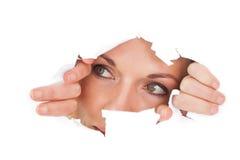 Femme regardant par le papier déchiré Image libre de droits