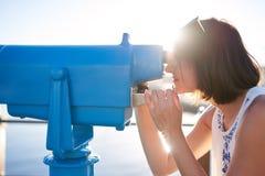 Femme regardant par un télescope bleu de fer Images stock
