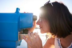Femme regardant par un télescope bleu de fer Image stock