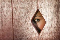 Femme regardant par un trou dans le mur images stock