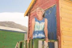 Femme regardant partie tout en se tenant la hutte de plage Image libre de droits
