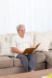 Femme regardant son album photos Images stock