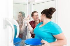 Femme regardant son ami nettoyant le verre de fenêtre photo libre de droits