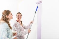 Femme regardant son ami peignant le mur photographie stock
