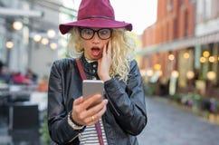 Femme regardant son téléphone dans le choc image stock
