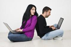 Femme remarquant dans son ordinateur portatif de mari Image stock