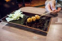 Femme remettant tenant un bâton de boulette de viande grillée dans le dippi épicé image stock
