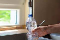 Femme remplissant bouteille en plastique avec de l'eau Image libre de droits