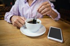 Femme remuant le café tout en se reposant à la table dans la boutique de café Photo stock