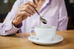 Femme remuant le café tout en se reposant à la table en café Images stock