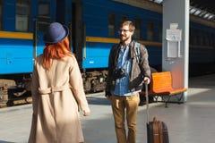 Femme rencontrant son ami de son voyage à la station de train Homme de touristes avec des camers de bagage et de photo concept de Photos stock