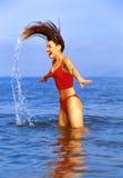 Femme renversant le cheveu dans l'océan photographie stock