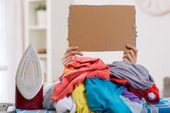 Femme repassant, caché par la grande pile de la blanchisserie image stock