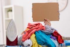 Femme repassant, caché par la grande pile de la blanchisserie photo libre de droits