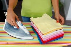 Femme repassant les chemises colorées Photos libres de droits