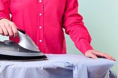 Femme repassant une chemise Photographie stock libre de droits