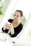 Femme reposée à la table vérifiant le téléphone portable Photos libres de droits