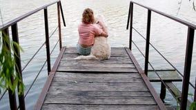 Femme reposant n le ponton avec son Labrador banque de vidéos