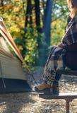 Femme reposant sur la table de pique-nique en dehors de la tente sur le terrain de camping sur des cris photographie stock