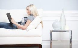 Femme reposant sur le divan avec un livre Photos stock