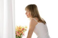 Femme restant à côté de l'hublot Photo stock