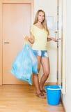 Femme restant à la porte avec des sacs de déchets photos libres de droits