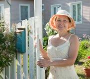 Femme restant à la porte d'une maison de campagne Photos stock