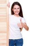 Femme restant le panneau en bois proche Image stock