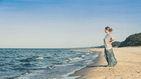 Femme restant sur une plage Photographie stock