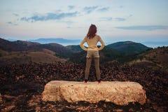 Femme restant sur une roche Image stock