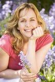 Femme retenant à l'extérieur le sourire de fleurs Photo libre de droits