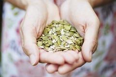 Femme retenant la poignée de noix et de graines photos libres de droits