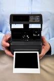 Femme retenant la trame de blanc d'appareil-photo instantané. Photographie stock