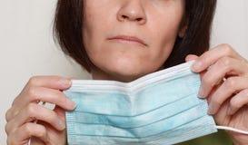 Femme retenant le masque de grippe Photographie stock libre de droits