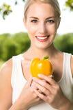 Femme retenant le poivre jaune Photo stock