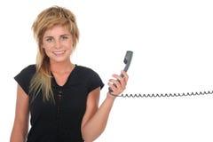 Femme retenant un combiné téléphonique de téléphone Photographie stock libre de droits