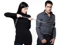 Femme retenant un homme enchaîné Photographie stock